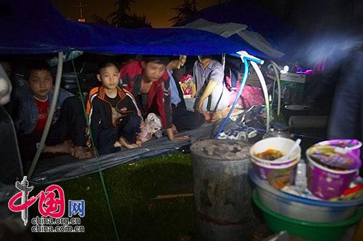 5月13日夜,四川省都江堰市災區,孩子們擠在一個塑膠布做的篷棚為家。 李肖軍/攝影