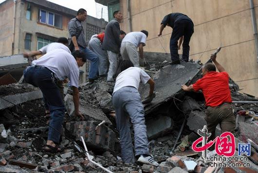 5月13日上午,四川都江堰市聚源镇中学,奋战了一夜的人们仍然在废墟里寻找幸存者。