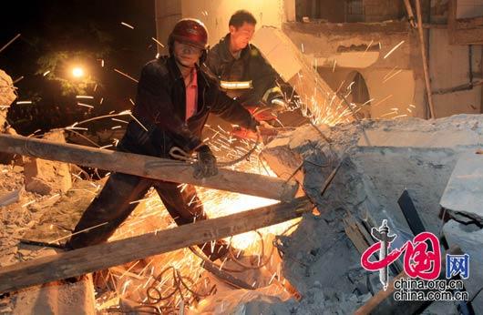 5月12日夜,四川都江堰市聚源镇中学,救援人员用各种办法清理废墟,解救埋在下面的幸存者。