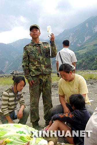 5月14日,刚刚抵达的解放军战士在四川省汶川县映秀镇漩口中学前为受伤群众举吊瓶