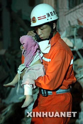 5月14日晚,消防抢险队员在四川绵竹市汉旺镇将1岁女孩沈天奇从废墟中成功救出。