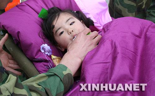 """5月14日,救援人员在喂宋欣宜喝牛奶。 当日9时40分左右,北川县城,被压在垮塌的房屋下的三岁小女孩宋欣宜,在已经逝去的父母身体翼护下与死神抗争了四十余个小时后终于获救。解放军官兵立即将小女孩放到担架上,往城外救护车能行驶的地方转运。 10时15分,担架来到了道路中断的三道拐处,在道路中断的地方站着一群人,抬小女孩的担架员一边高呼""""让开、让开"""",一边急速地往前冲。人们让开了一条路,这时才看见,人群中还有来灾区视察的温总理! 温总理来到小欣宜身边亲切地进行了慰问,由于病情紧急,担架并没有过多停留就继续前行。两分钟后,小欣宜被抬上了来自洛阳协和医院的救护车,送往医院救治。"""