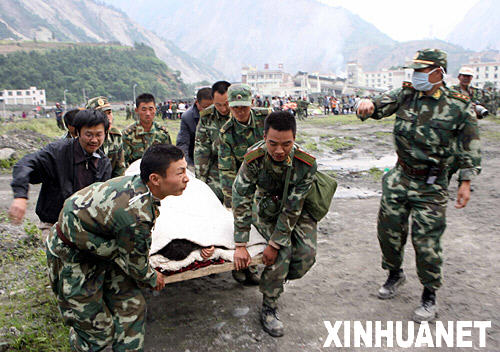 5月14日,武警官兵在汶川县映秀镇将受伤的群众抬上直升飞机