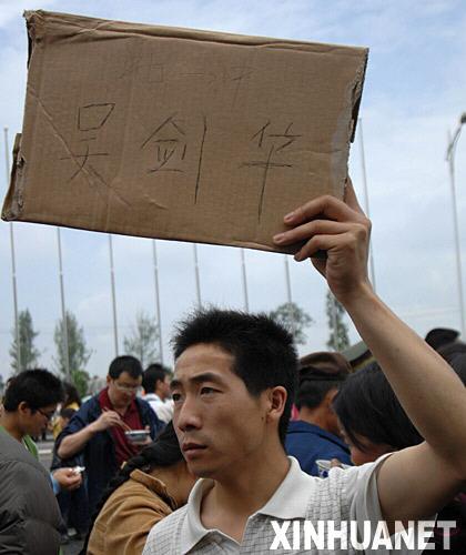 5月14日,一位市民在四川绵阳市九洲体育馆前举着牌子找人