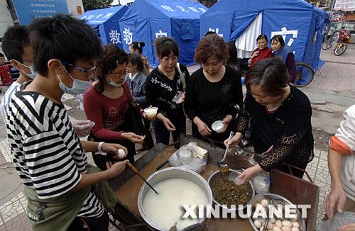 5月15日上午,绵阳市下岗职工程兰(右一)等人自发出钱、出力为灾民做饭送饭