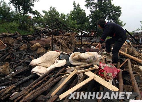 5月14日,四川绵竹市遵道镇居民在废墟中抢救财产