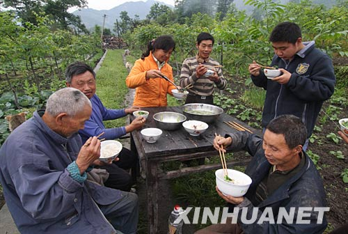 5月14日,四川绵竹市遵道镇的几户居民一起在废墟旁就餐