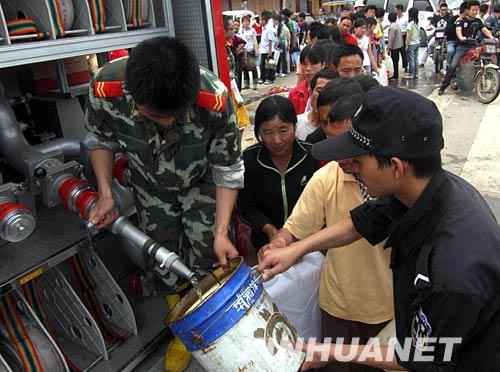 5月14日,四川绵竹市汉旺镇居民在消防车前排队取水