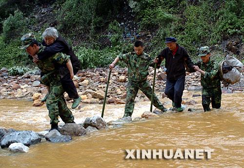 5月15日,解放军战士从交通中断的绵竹市清平乡背出老人,正在过河
