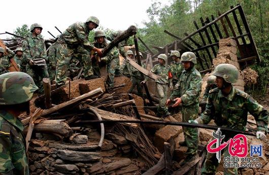 5月15日下午,甘肃陇南碧口镇,武警士兵们正在清理震后房屋的废墟。 田蹊/摄影