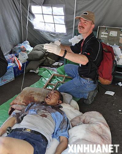 5月14日,来自美国的医学博士孙柏安在北川县协助医生救治伤员。