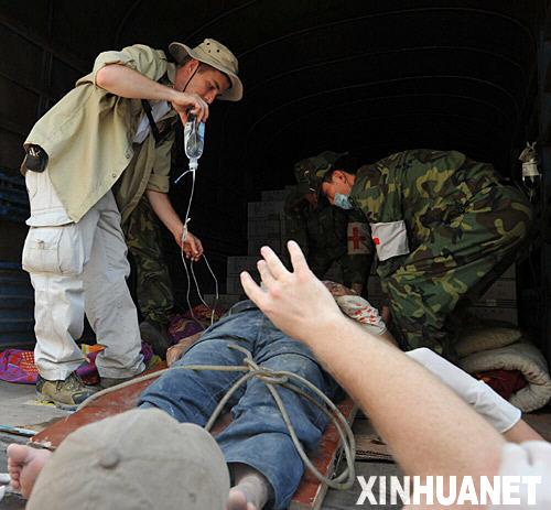 5月14日,来自美国的留学生郭爱德(左)在北川县协助医生救治伤员