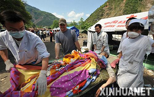 5月14日,来自美国的留学生牧勇士(左二)在北川县与医护人员一起运送伤员