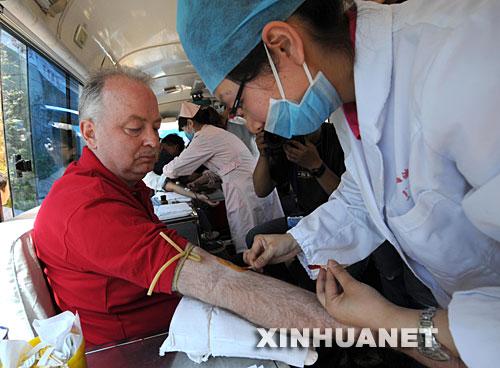 5月14日,53岁的加拿大友人迈克尔·普尔在流动献血车上义务献血