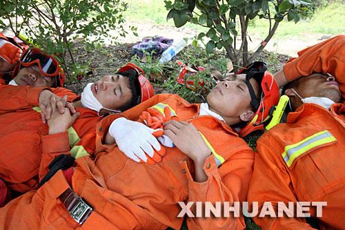 5月16日,几名疲惫的救援人员在路边稍作休息。在四川省重灾区北川进行抗震救灾的解放军战士、武警官兵等救援人员正夜以继日地搜救灾民,累了,就在路边稍作休息,醒来,继续投入新的战斗。 新华社记者高学余摄