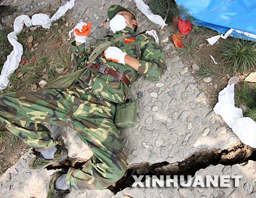 5月16日,一位解放军战士在路边稍作休息。在四川省重灾区北川进行抗震救灾的解放军战士、武警官兵等救援人员正夜以继日地搜救灾民,累了,就在路边稍作休息,醒来,继续投入新的战斗。 新华社记者高学余摄