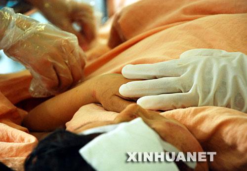 5月15日,成都华西医院的医护人员摸着伤员的手,给他鼓励。 在四川地震灾区,解放军、武警、公安、边防、消防官兵以及民兵、医疗救护人员和志愿者们,不怕危险,不畏疲劳,为抢救每一条宝贵的生命连续奋战。他们是最可爱的人。 新华社发(徐媛媛 摄)
