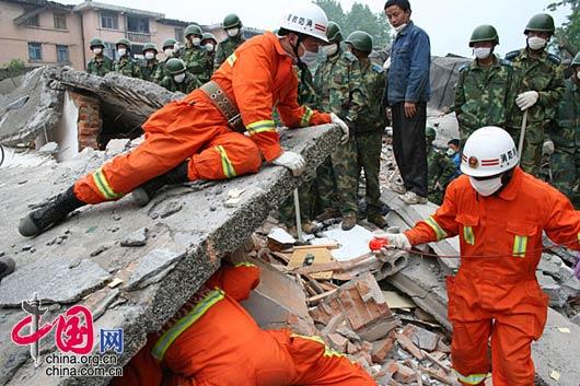 为了信号更加准确,消防队员不顾危险,将身体探入废墟中。武越明/摄影