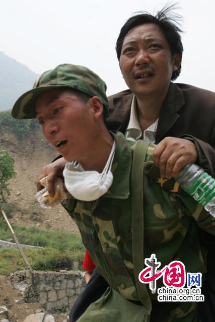 2008年5月16日,四川北川灾区,解放军战士将灾民背送医疗点进行救治