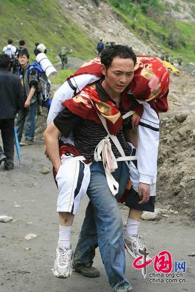 5月15日映秀镇,一位父亲徒步将遇难的女儿背出。 朱建国/摄影