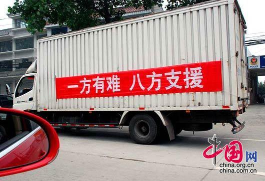 5月17日,在从成都前往绵竹九龙镇、汉旺镇的路上,援助车上写着:一方有难,八方支援。 杨恒/摄影