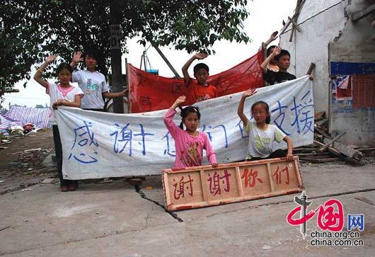 5月17日,绵竹市九龙镇,灾区的孩子们向援助者致意。 杨恒/摄影