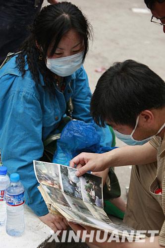 5月18日,受困者亲属在绵竹市汉旺镇搜救现场翻看从废墟里找到的家庭相册。