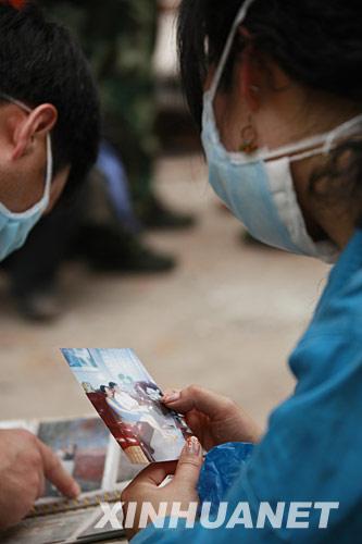 5月18日,一名受困者亲属手握母亲的照片守候在绵竹市汉旺镇搜救现场