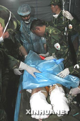 在汶川县映秀镇,山东公安消防总队救援官兵不顾多次余震和房屋随时坍塌的危险,经过长达56个小时的营救,于18日20点10分,将被埋149个小时40分钟的汶川映秀镇电厂女职工虞锦华成功救出。 这是中国人民解放军第三军医大学新桥医院和深圳医疗队的医护人员在对虞锦华进行联合抢救。