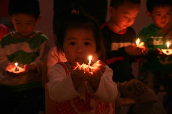图文:幼儿园小朋友点起蜡烛进行祈祷