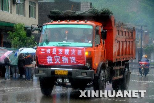5月13日,在通往四川北川县的公路上,救灾物资正冒雨源源不断运往灾区。