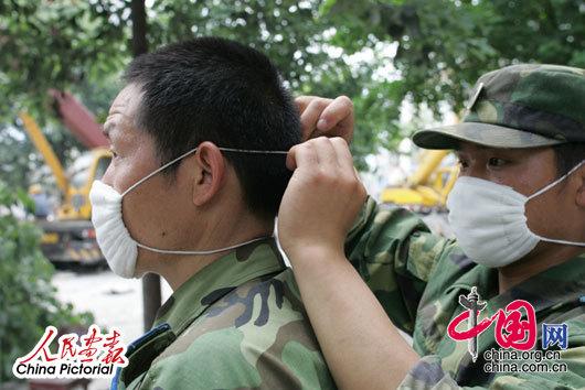 2008年5月14日,四川都江堰,搜救现场会扬起大量尘土,参与救援的解放军战士在互相帮忙带起口罩进行更深入的搜寻工作。