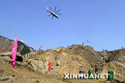 5月27日,运输工程物资的直升机在北川唐家山堰塞湖上方飞行。