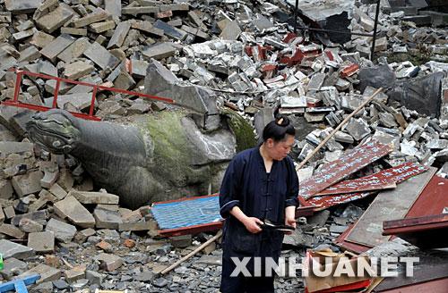 5月26日,一名道士在都江堰景区的废墟中寻找东西。