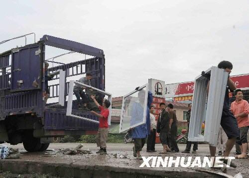 5月29日,在四川省安县黄土镇,人们正在搬运活动板房材料。