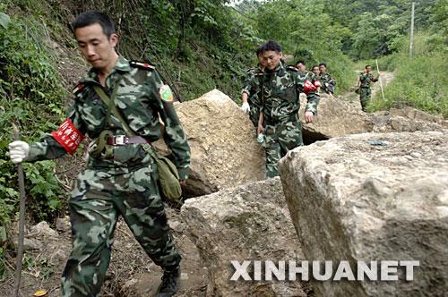 6月2日,来自成都印钞公司的民兵在都江堰市赵公山附近搜寻5月31日失事的直升机。