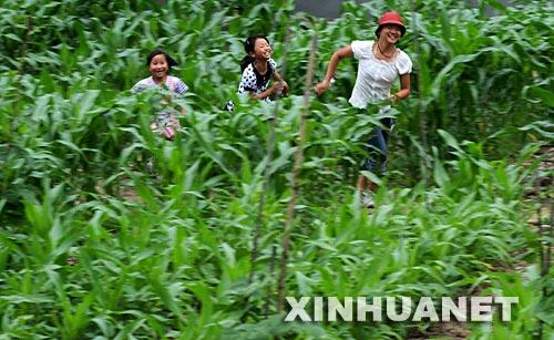 6月8日,几位女孩正在映秀镇受灾群众安置点旁的玉米地里奔跑。处在震中的汶川县映秀镇,在地震后一度成了一座废墟。震后随着解放军战士、各行各业志愿者的到来,救援物资源源不断地输入,临时医院、临时小学、帐篷超市的出现,留守在映秀镇的群众从废墟中清理出建筑材料自建简易房,积极展开生产自救,在安置区里勇敢地开始了新生活。 新华社记者 李尕 摄
