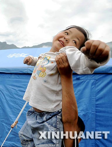 6月7日,在映秀镇受灾群众安置点,一名男孩正把妹妹高高举过帐篷顶。处在震中的汶川县映秀镇,在地震后一度成了一座废墟。震后随着解放军战士、各行各业志愿者的到来,救援物资源源不断地输入,临时医院、临时小学、帐篷超市的出现,留守在映秀镇的群众从废墟中清理出建筑材料自建简易房,积极展开生产自救,在安置区里勇敢地开始了新生活。 新华社记者 李尕 摄