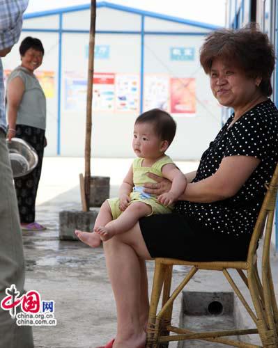 坐在家门口的外婆抱着可爱的孙女