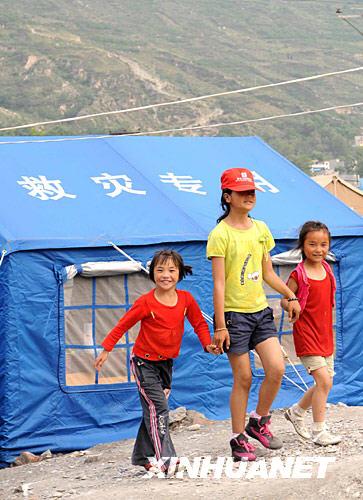 6月10日,阿坝州儿童福利院的三个孩子走在帐篷营地前