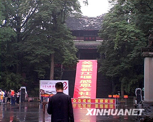 6月14日,一名游客站在都江堰景区的伏龙观前。
