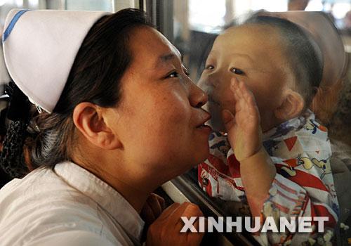 6月18日,一位护士与来自四川灾区的孩子告别。 当日,51名在山西接受救治后痊愈的四川地震灾区伤员集体从太原乘火车返回故乡。自5月28日以来,山西共接收两批198名来自四川地震灾区的伤员。 新华社记者 彭洋摄