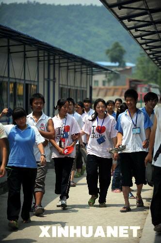 6月28日,北川中学高三学生走在活动板房教室前。目前,在北川中学新校园——长虹培训中心学习生活的589名北川中学高三学生正在紧张复习,平静地迎接高考。四川和甘肃地震灾区高考将在7月3日到5日举行。