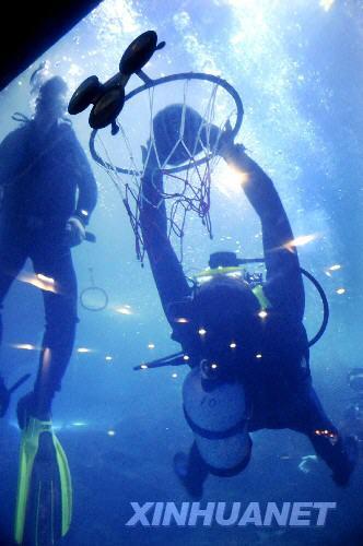 """6月28日,一名选手在海底扣篮比赛中展示""""反身扣篮""""绝技。当晚,""""中国加油—2008海底奥运争霸赛""""在青岛海底世界开赛,来自青岛、济南、日照、潍坊、南京等城市的潜水爱好者在海底进行的射击、扣篮、吊环、举重、接力等项目中激烈角逐,尽情体验水下竞技的乐趣。"""