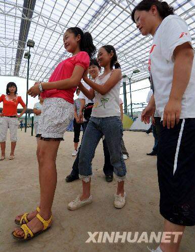 """6月25日,中科院心理所绵竹工作站的心理援助志愿者在指导灾区临时学校的学生做""""信任背摔""""游戏,以增强学生的信任与责任感。"""