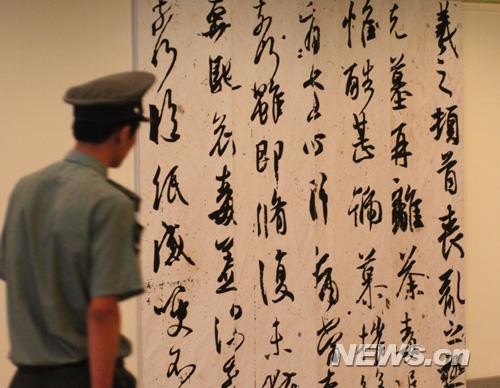一名保安正在欣赏书法作品   新华网 陈竞超摄-2008北京奥运图片