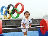 """7月28日,一名幼儿在社区的奥运文化广场上""""尝试举重""""。"""