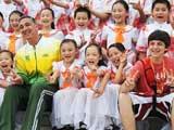 """8月4日,北京市中关村三小""""同心结""""合唱团的学生在北京奥运村升旗广场与巴西代表团成员合影。"""