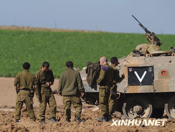 1月6日,在加沙地带中部边境,以色列士兵在装甲车旁休息。新华社记者 殷博古摄