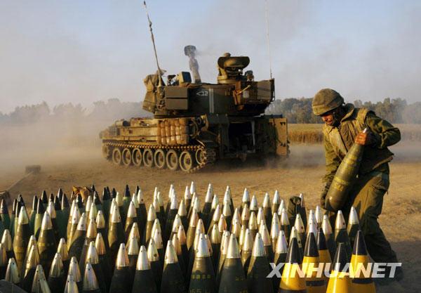 这是2006年6月28日,在加沙地带附近的纳哈勒奥兹,一名以色列士兵为一门正在向加沙地带开火的自行火炮运送炮弹。